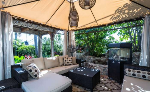 An entertaining area is covered by a cabana, perfect for relaxing with a book or hosting a back yard barbecue.
