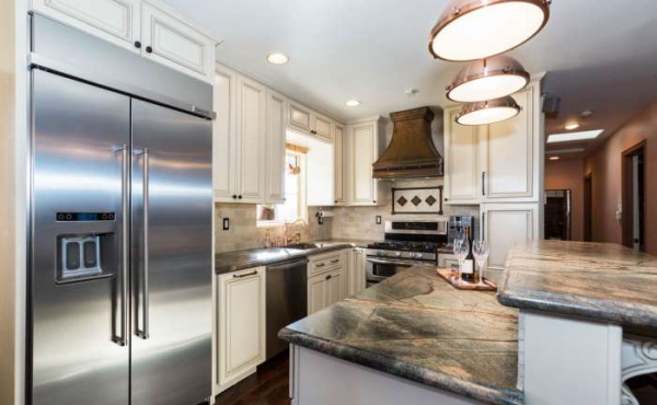 The custom designed kitchen features rain forest marble counters with antique glazed cabinetry.